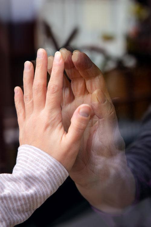 Hände berühren sich durch Fensterscheiben